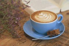 咖啡、花和书在咖啡店 免版税库存图片