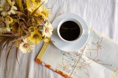 咖啡、花盆和地图在桌上 免版税库存照片