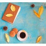咖啡、葡萄酒书、麦甜饼和秋叶在木背景-放松或退休概念与大方的本体空间 免版税库存照片