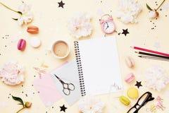 咖啡、蛋白杏仁饼干、闹钟、办公用品、牡丹花和空的笔记本 时尚妇女运转的书桌 r 库存图片