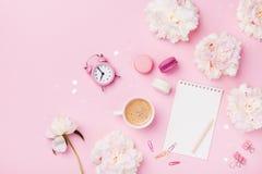 咖啡、蛋白杏仁饼干、闹钟、办公用品、牡丹花和空的笔记本 时尚妇女运转的书桌 r 库存照片
