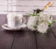 咖啡、蛋白杏仁饼干在茶碟和花花束  免版税库存照片
