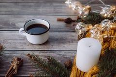 咖啡、蜡烛、爆沸、桂香、云杉的分支和温暖的橙色围巾和用在木桌上的被带领的光装饰 图库摄影