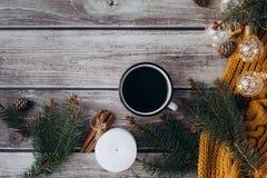 咖啡、蜡烛、爆沸、桂香、云杉的分支和温暖的橙色围巾和用在木桌上的被带领的光装饰 免版税图库摄影