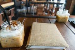咖啡、被冰的咖啡上等咖啡和迷离菜单书在桌木头backg 免版税库存照片