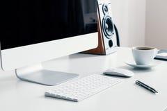 咖啡、键盘和台式计算机在书桌上在白色家庭办公室内部 实际照片 免版税库存照片