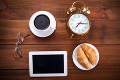 咖啡、闹钟、玻璃、数字式片剂和新月形面包 免版税库存照片