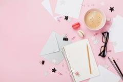 咖啡、macaron、办公用品和干净的笔记本在桃红色淡色台式视图blogging的 平的位置样式 美丽的早餐 免版税库存图片