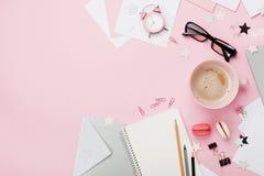 咖啡、macaron、闹钟、办公用品和笔记本在桃红色淡色台式视图 平的位置 妇女博客作者运转的书桌 免版税库存照片