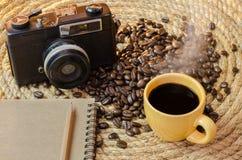 咖啡与一个老照相机笔记本的在黄麻绳索 免版税库存照片