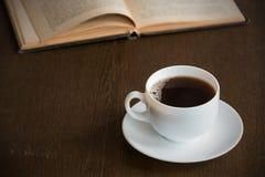 咖啡与一本书的在难看的东西木桌上 免版税库存照片