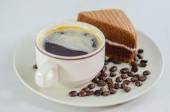 咖啡与切片的在白色背景的巧克力蛋糕 免版税库存图片