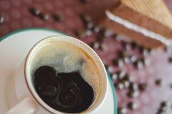 咖啡与切片的在盘子背景的巧克力蛋糕 免版税库存图片