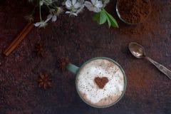 咖啡与可可粉、桂香和春天的心脏的在黑暗的石背景开花 库存图片