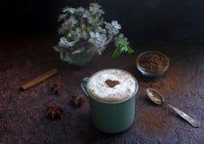 咖啡与可可粉、桂香和春天的心脏的在黑暗的石背景开花 免版税库存照片