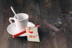 咖啡与唇膏标记的和笔记& x27; 我爱you& x27;在桌上 库存图片