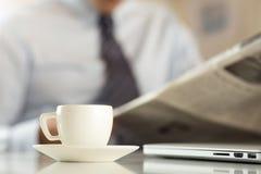 咖啡与商人读书报纸的在背景 库存图片
