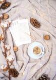 咖啡与心脏形状的日志,棉花页写的新的计划或购物礼物,分支,杉木锥体和坚果  库存图片