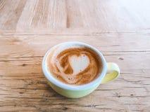 咖啡与心脏样式的在土气的一个五颜六色的杯子求爱 库存照片