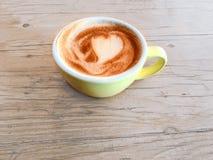 咖啡与心脏样式的在土气的一个五颜六色的杯子求爱 图库摄影