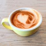 咖啡与心脏样式的在土气的一个五颜六色的杯子求爱 库存图片