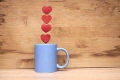 咖啡与心脏的在木背景 免版税库存图片