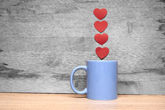 咖啡与心脏的在木背景 免版税库存照片