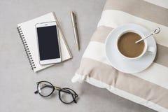 咖啡与手机、玻璃和笔记本的 免版税库存照片