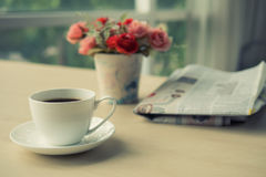 咖啡与报纸的在桌上在晴朗的早晨,温暖的口气 免版税库存图片
