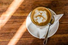 咖啡与拿着爱心脏,在木桌上的熊的拿铁艺术的拿铁 免版税库存照片