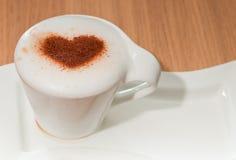 咖啡与桂香心脏的在牛奶泡沫 免版税库存照片