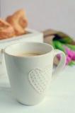 咖啡与桃红色郁金香和新月形面包花束的  库存图片