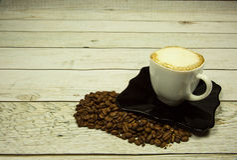 咖啡与泡沫的和在一个木工作台面的咖啡豆 库存图片