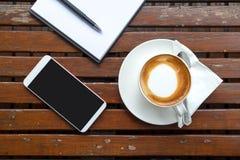 咖啡与白皮书和智能手机的投入了木桌 免版税库存照片