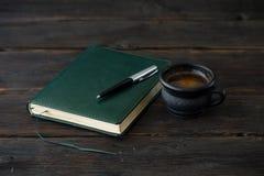 咖啡与笔记本的在黑暗的木桌上 免版税库存图片