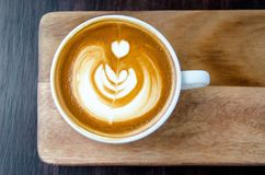 咖啡与美好的拿铁艺术的在有黑色的木板材 库存图片