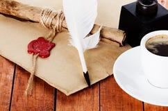 咖啡与翎毛钢笔和墨水池羊皮纸纸卷的 库存照片