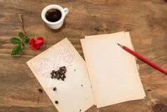 咖啡与飞过的心脏的在白色板料的和笔 免版税库存照片