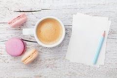 咖啡与macaron的和在从上面白色木桌上的空白纸,平的位置 免版税图库摄影