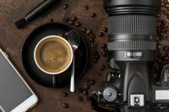 咖啡与MOBIL电话的在土气背景的和照相机 库存照片