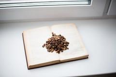 咖啡五谷在开放书的在窗台 免版税库存图片