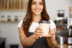 咖啡企业概念-微笑对照相机的美丽的白种人夫人提供一次性拿走热的咖啡在 图库摄影