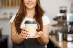 咖啡企业概念-微笑对照相机的美丽的白种人夫人提供一次性拿走热的咖啡在 免版税库存图片