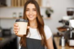 咖啡企业概念-微笑对照相机的美丽的白种人夫人提供一次性拿走热的咖啡在 库存照片