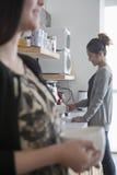 咖啡休息的两名女实业家在办公室 库存图片