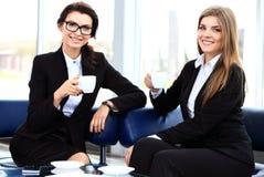 咖啡休息的,享受聊天的妇女办公室工作者 免版税库存照片