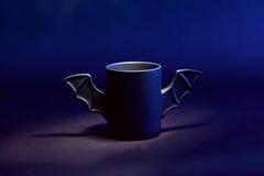 咖啡作为棒的为在黑背景的万圣夜 蓝色光和阴影 玩具 概念 免版税图库摄影