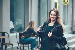 去咖啡作为 佩带在黑时髦的衣裳的美丽的年轻都市妇女举行咖啡杯和微笑 库存图片