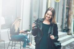 去咖啡作为 佩带在黑时髦的衣裳的美丽的年轻都市妇女拿着咖啡杯和微笑,当走时 免版税库存照片