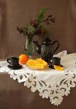 咖啡具、桔子和糖果在一块白色餐巾 图库摄影